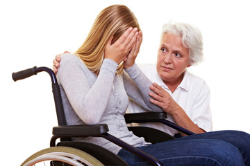 Krankenpflegerin tröstet Frau im Rollstuhl