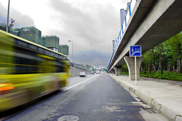 High-speed vehicles blurred trails on urban roads under overpass