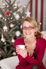 lächelnde frau mit tasse kaffee vor dem weihnachtsbaum