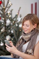 frau schreibt sms vor dem weihnachtsbaum