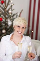 blonde frau mit sekt vor dem weihnachtsbaum