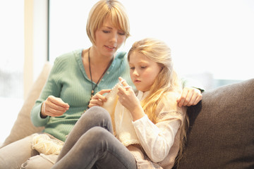 Mother and daughter sitting on sofa knitting