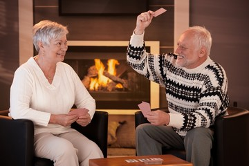 Retired couple playing cards in front of fireplace