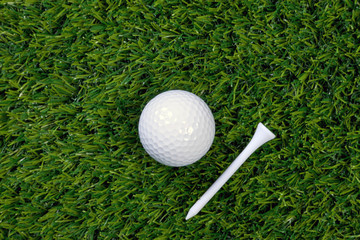 Golf ball and tee on grass