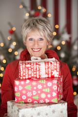 lachende seniorin mit weihnachtsgeschenken