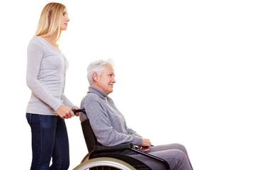 Pflegerin schiebt Frau im Rollstuhl