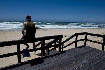 Guy sitting looking at ocean