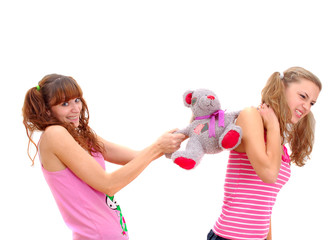 two teenage sisters quarrelling about teddy bear