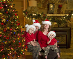 Family of four with santa hats sits beside christmas tree