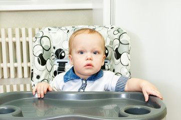 The kid sits in a highchair