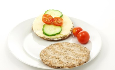 Cracker on plate, with tomato and cucumber, white background