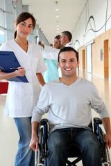 Beautiful nurse standing by man in wheelchair