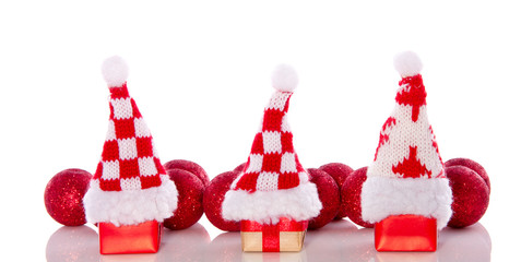 three christmas hats on little presents in gront of christmas ba