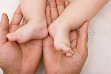 Babies foot and hand of man