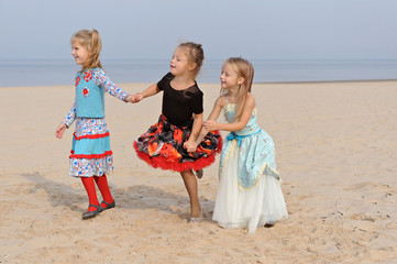 three litlle girls holding hands on the beach