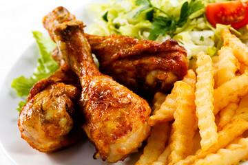 Grilled chicken drumsticks, chips and vegetables