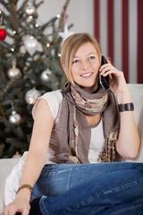blonde frau mit telefon vor dem christbaum
