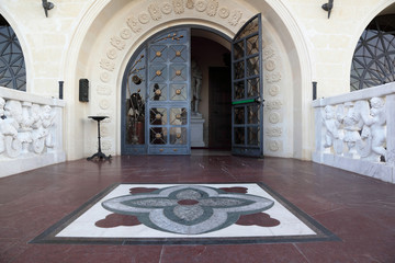 Entrance with  large arched glass door, decorated  forged colors