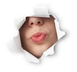 Beautiful young woman sending a kiss through a hole