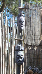Pair of african masks displayed on a wooden post, at a zoo