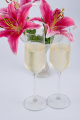 Two glasses of champagne and pink lily