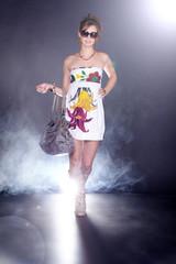 Hübsche Frau mit Handtasche auf dem Laufsteg