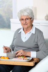 Elderly woman sitting in sofa  with lunch tray