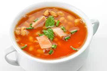 bean soup with ham and tomatoes in a white soup cup