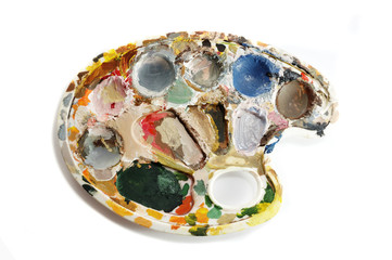 Dirty artist's palette with paints on white background