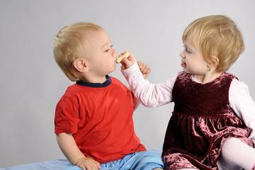baby girl and boy eating food