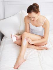 Woman applying cream for skin on legs
