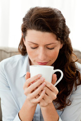 Pretty woman smelling her coffee on the sofa at home