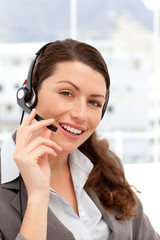 Beautiful businesswoman with headphones and smiling at camera