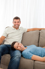 Portrait of a cheerful couple resting together on the sofa
