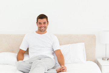 Happy man relaxing on his bed at home