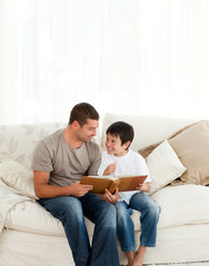 Adorable boy looking at a photo album with his father
