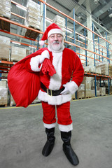 Happy Santa Claus with red sack in storehouse