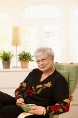 Senior lady having tea at home