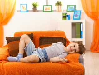 Cute kid relaxing on sofa