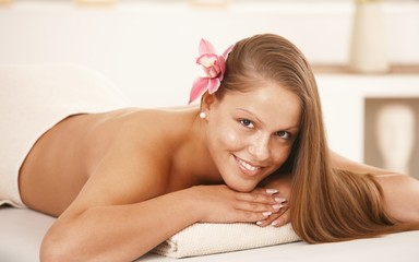 Beautiful young woman lying on massage bed