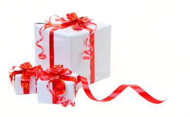 A white box tied with a red satin ribbon bow. A gift for Christm