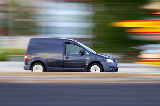Speedy  dark minivan  is  going on road, panning and blur