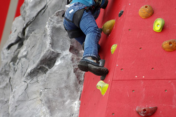 Child climbing on a wall in a climbing center