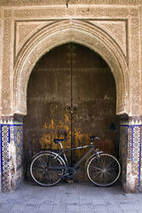 Bicycle leaning against door under archway