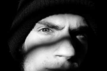 Young man with beanie in shadows