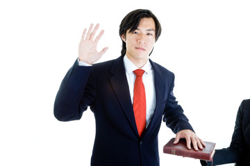 Asian Man Raise Hand Swearing on Bible Isolated White Background