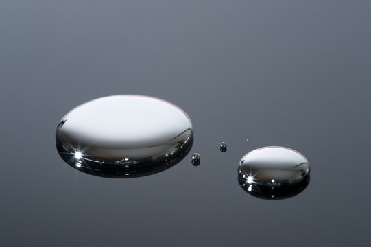 Droplets of mercury on a reflective surface.