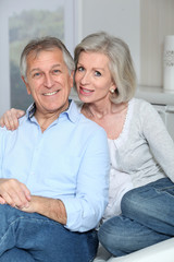Portrait of happy senior couple sitting in sofa