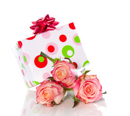a cheerful gift on top of three pink orange roses isolated over