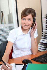 Young woman in office with headset